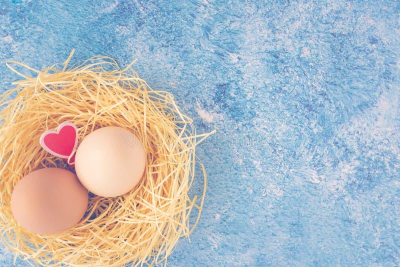 两个新鲜的鸡鸡蛋顶视图在秸杆巢和装饰木心脏在蓝色背景 愉快复活节的问候 免版税库存照片