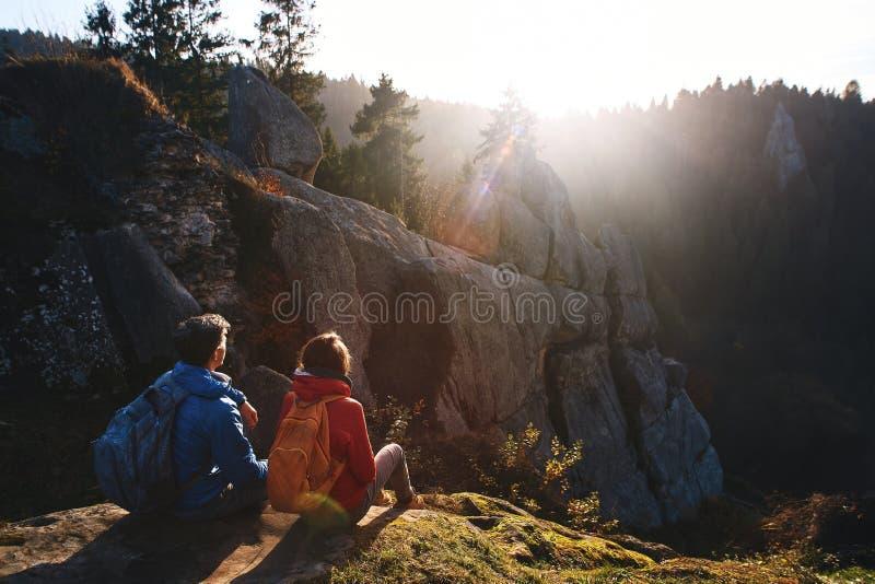 两个旅客坐峭壁的边缘反对树木繁茂的小山和多云天空在日出 男人和妇女招呼 免版税库存照片
