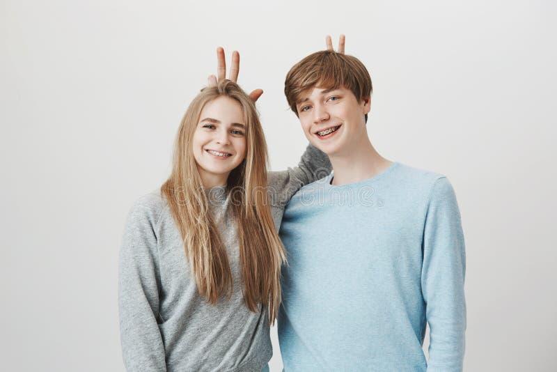 两个最好的朋友一起从学校 滑稽的快乐的人和女孩有公平的头发的,广泛地微笑对照相机,佩带 免版税库存图片