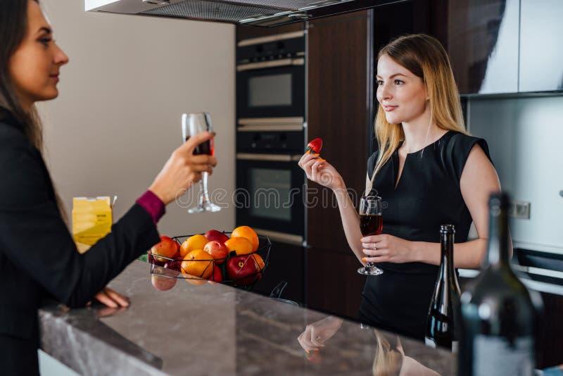 两个最好的朋友有一点乔迁庆宴党通过喝站立的红葡萄酒在厨房 库存照片