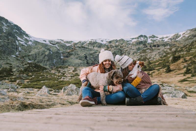 两个朋友使用与他们的坐在有一座大山的草甸的狗在他们后 免版税库存照片