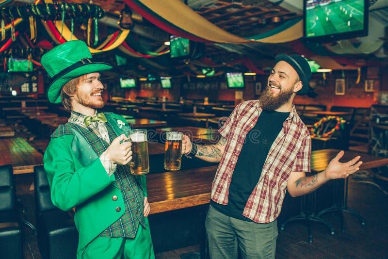 两个朋友在客栈微笑站立 他们拿着杯子啤酒 左穿戴saitn帕特里克的衣服的人 他们愉快看其中每一 库存照片