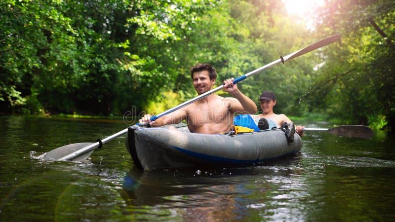 两个朋友在狂放的密林河的皮船游泳 免版税库存照片