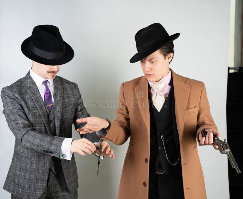 两个朋友在葡萄酒衣裳穿戴了并且描述减速火箭的探员和间谍英国经典样式的在白色演播室背景 库存照片