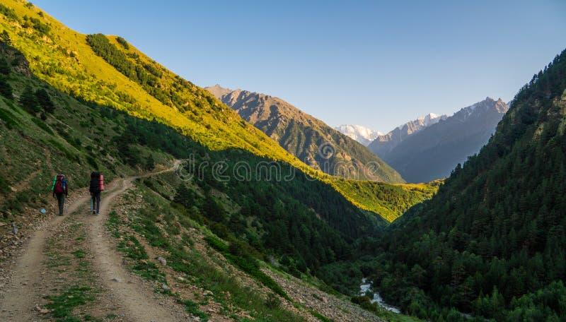 两个朋友在高加索山脉步行 对Elbrus的轨道-高山在欧洲 免版税库存图片
