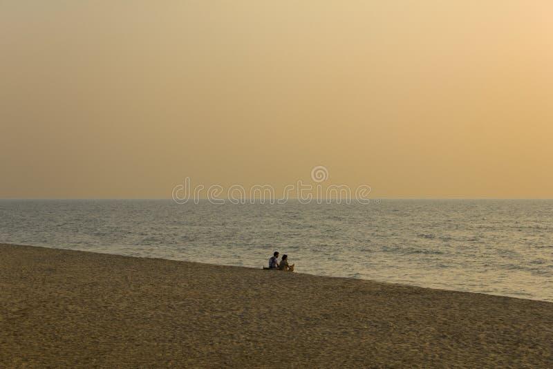 两个朋友坐一个沙滩以海洋和灰色明亮为背景 库存图片