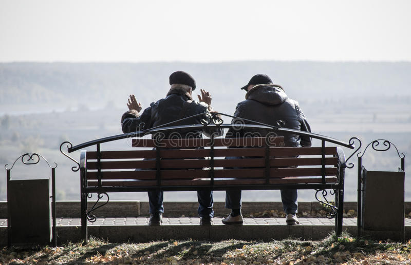 两个朋友坐长凳 库存图片