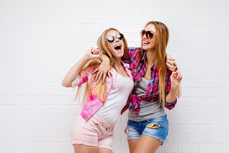 两个朋友摆在 现代的生活方式 两个时髦的性感的行家女孩最好的朋友准备好党 女孩朋友 免版税库存图片