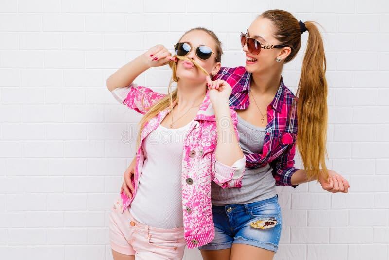 两个朋友摆在 现代的生活方式 两个时髦的性感的行家女孩最好的朋友准备好党 女孩朋友 库存图片