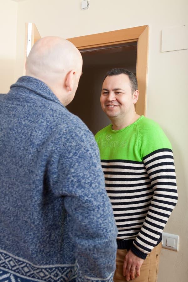 两个朋友谈话在门附近 库存照片