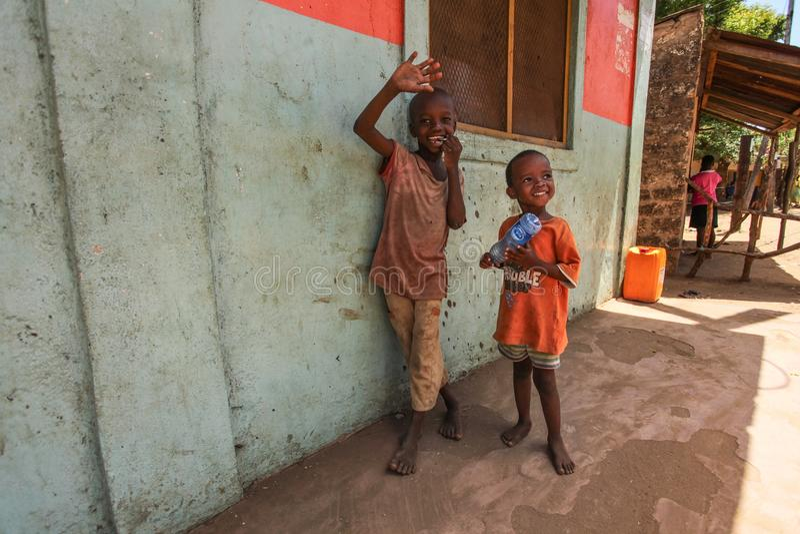 两个未知的小男孩,站立在墙壁旁边,微笑和挥动对访问地方贫民窟的游人 许多孩子遭受在贫寒下 免版税库存照片