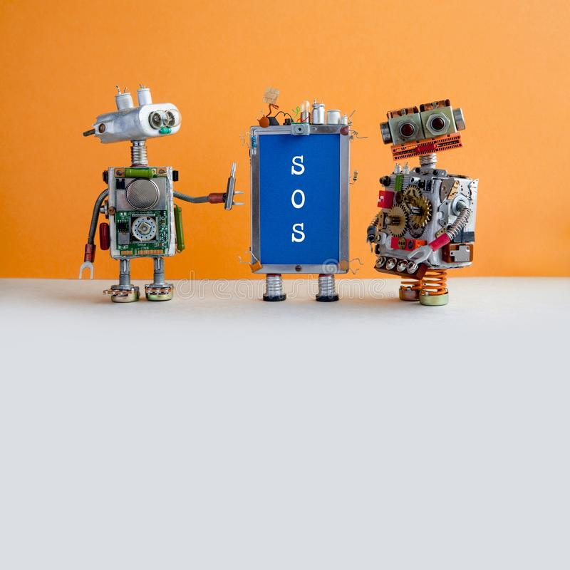 两个机器人handymans和智能手机有消息的SOS在蓝色屏幕上 复制空间 免版税库存图片