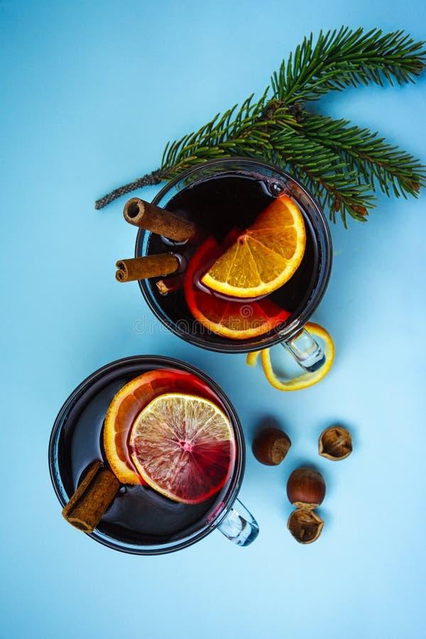 两个杯子与云杉的分支的被仔细考虑的在蓝色背景的酒和坚果 免版税库存照片
