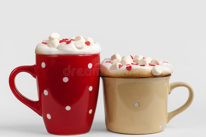两个杯子与蛋白软糖和糖心脏的热奶咖啡 免版税图库摄影