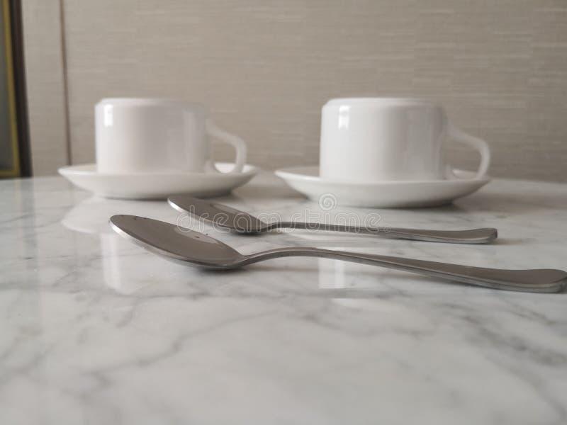 两个杯子和两把匙子在书桌上 免版税库存照片
