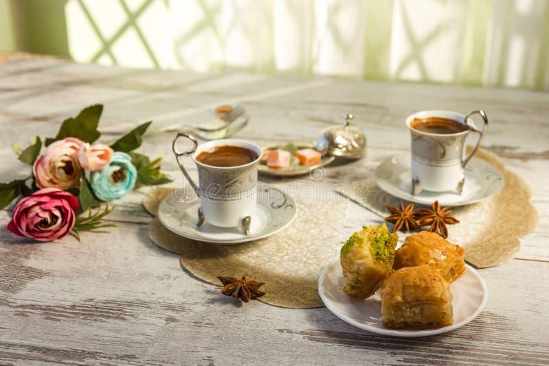 两个杯子土耳其咖啡和一块板材有果仁蜜酥饼的 库存图片