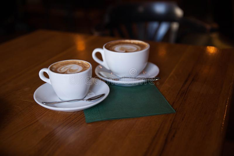两个杯子在一张木桌上的热奶咖啡 库存图片