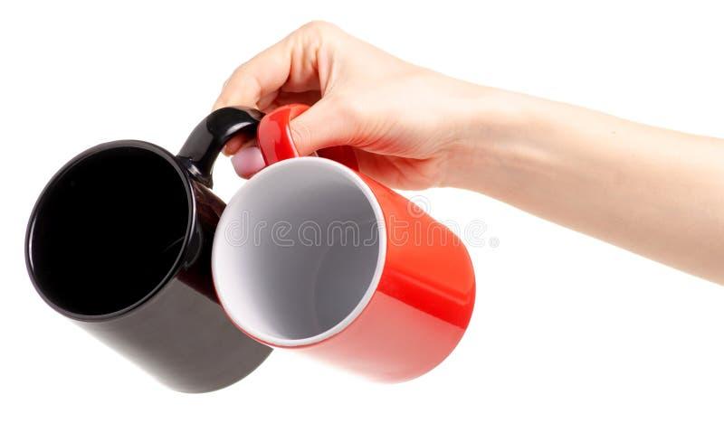 两个杯子在手中抢劫红色黑色 库存照片
