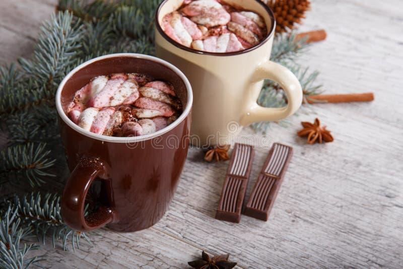 两个杯子甜可可粉用在杉木旁边的蛋白软糖在桌背景分支 巧克力热冬天 免版税库存图片