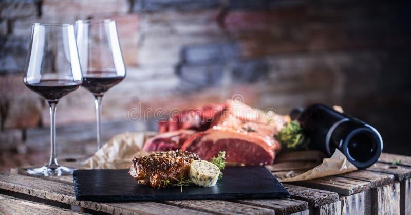 两个杯子用在板岩板的红葡萄酒烤和未加工的牛排 免版税图库摄影