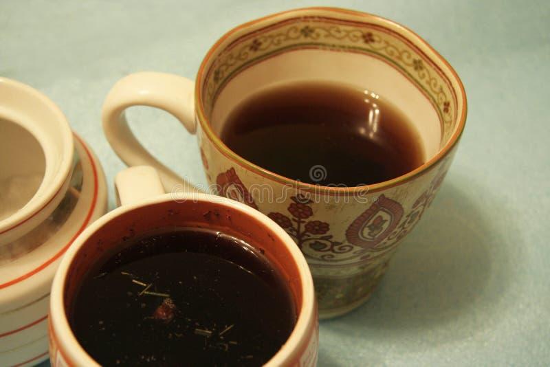 两个杯子用清凉茶和一个糖碗在浅兰的背景 图库摄影