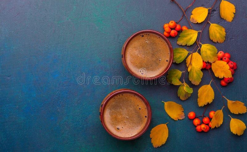 两个杯子秋叶绣线菊类的植物Vanhouttei无奶咖啡和分支用在黑暗的小红色花揪` s果子-蓝色-绿色pai 免版税库存图片
