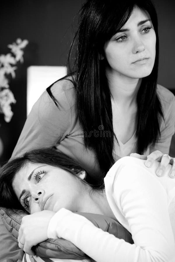 两个某人造成的姐妹深刻的哀痛死亡 免版税库存照片
