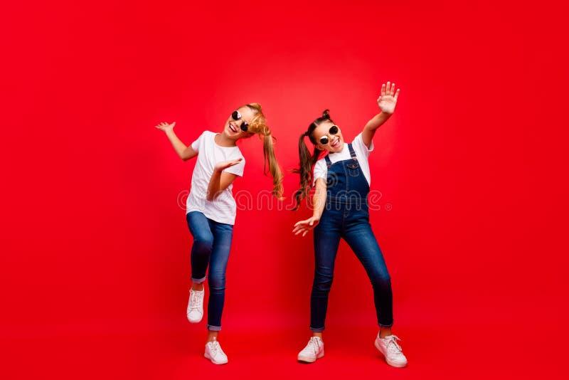 两个棕发女朋友在周末假日玩得开心的滑稽疯狂的全身照片惊呼 免版税图库摄影