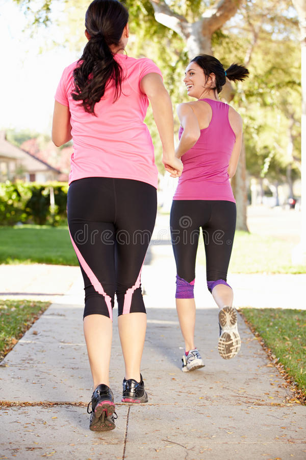 两个母赛跑者背面图在郊区街道上的 免版税库存图片