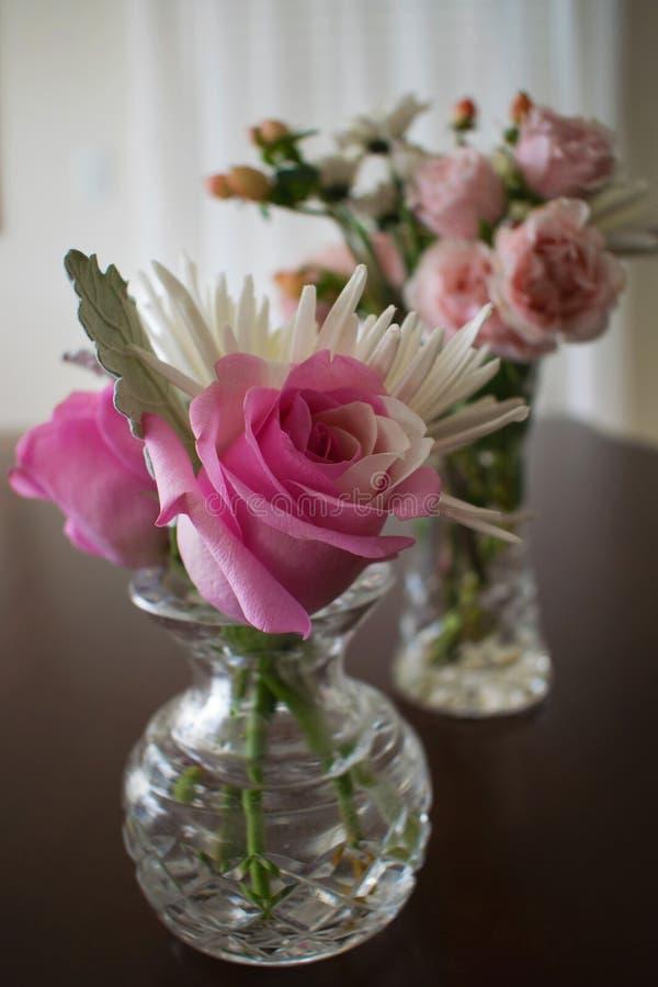 两个水晶花瓶用玫瑰和其他小花填装了 免版税库存照片