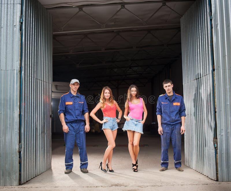 两个汽车机械师人和两个美丽的性感的女孩 免版税库存图片