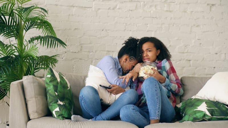 两个混合的族种卷曲女朋友坐在电视的长沙发和手表非常可怕电影和在家吃玉米花 库存图片