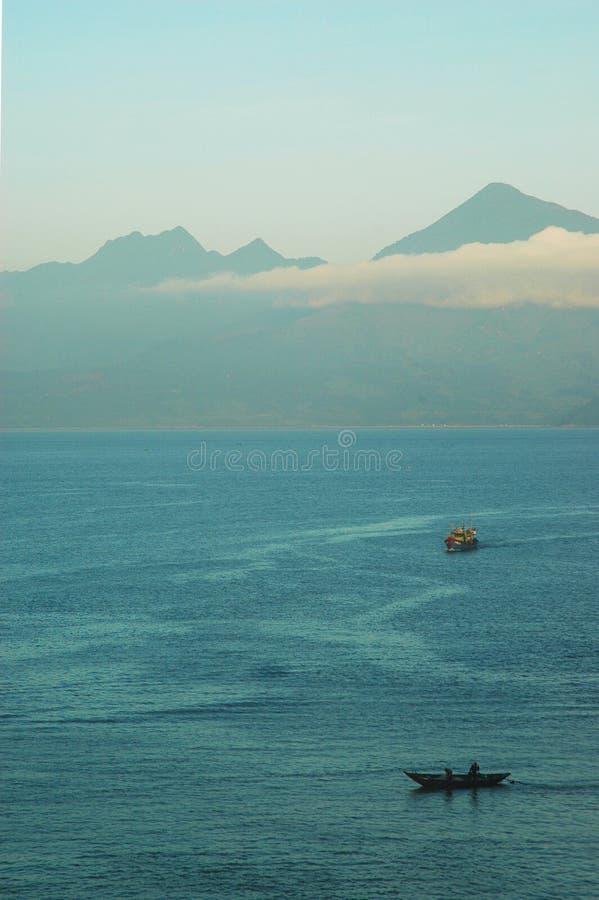 两个渔船在一个海湾的黎明在山附近 库存图片