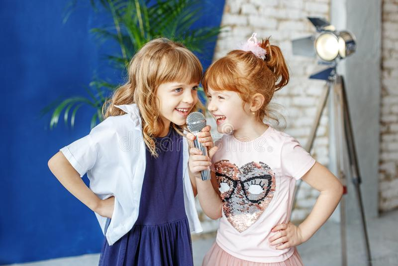 两个滑稽的孩子唱在卡拉OK演唱的一首歌曲 概念是childh 免版税库存照片