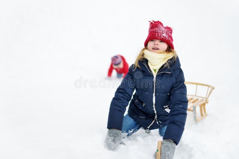 两个滑稽的小女孩获得与雪橇的乐趣在美丽的冬天公园 使用在雪的逗人喜爱的孩子 库存照片