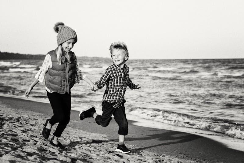 两个滑稽的白种人孩子哄骗演奏跑在海洋在日落的海海滩的朋友 库存照片
