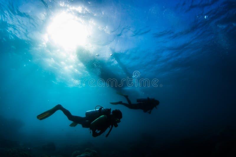 两个潜水者在热带海游泳在水面下 免版税库存照片