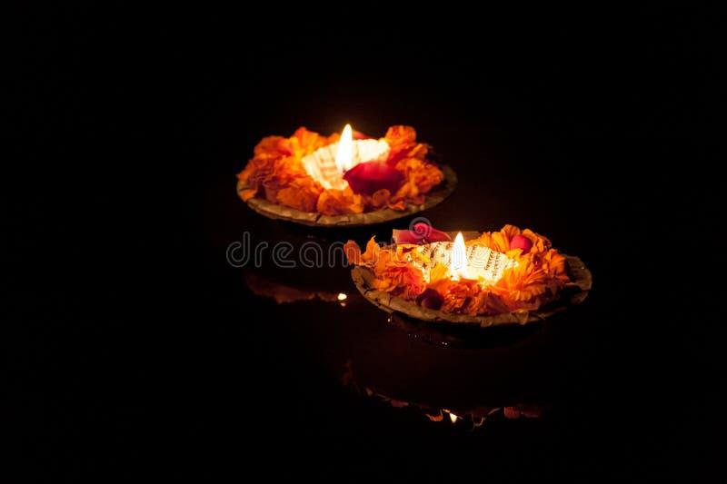 两个灼烧的pooja蜡烛在河恒河的晚上 库存图片