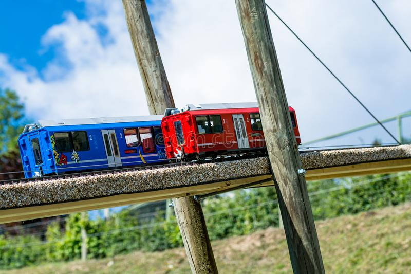 两个玩具机车,一蓝色和一红色,在一个木桥 免版税库存图片