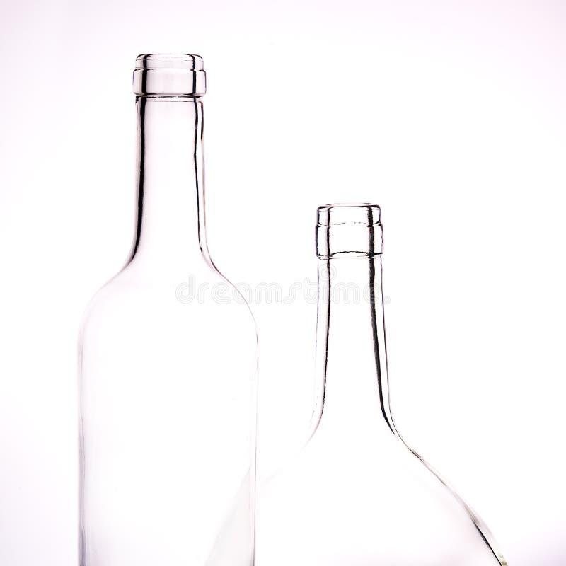 两个玻璃清楚的瓶在白色背景的另外大小 免版税库存图片