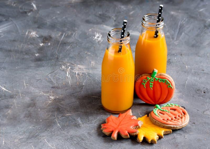 两个瓶南瓜汁用黑秸杆水平的照片万圣夜食物和甜点 库存照片