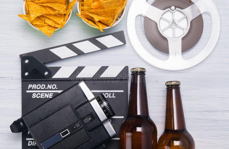 两个瓶啤酒、一个桶烤干酪辣味玉米片,有一老摄像头的一个电影拍板和影片小条 免版税图库摄影