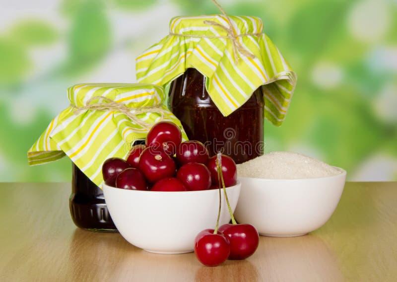 两个瓶子果酱关闭了有斑纹的纸、碗用樱桃和糖在桌上 图库摄影