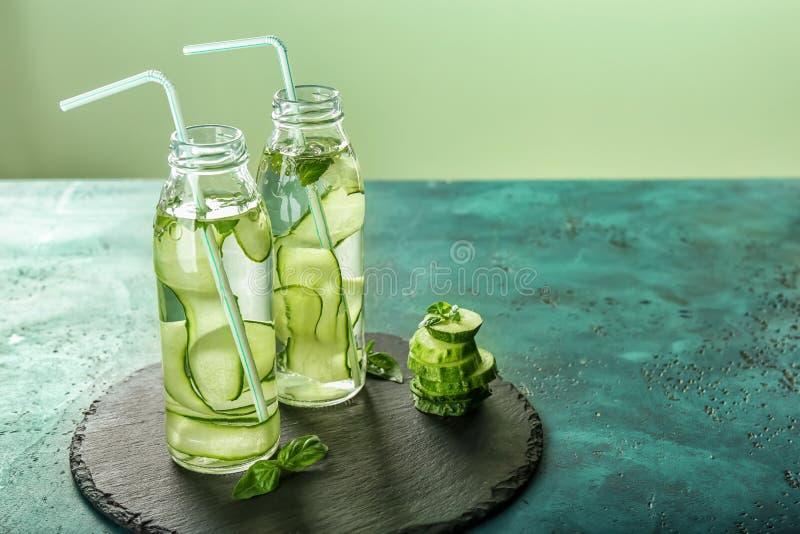 两个瓶黄瓜灌输了在桌上的水 免版税库存照片