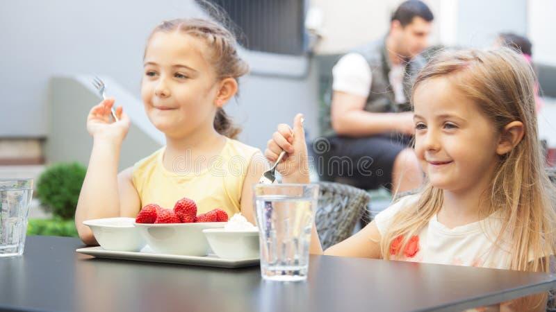 两个甜女孩在餐馆吃与crea的红色草莓 库存图片