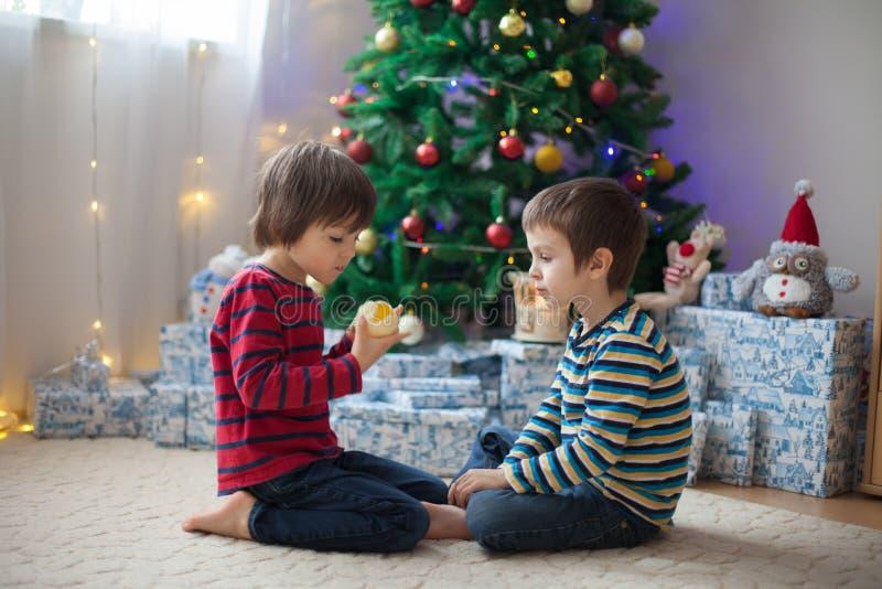 两个甜孩子,男孩兄弟,打开在圣诞节出席 免版税库存照片