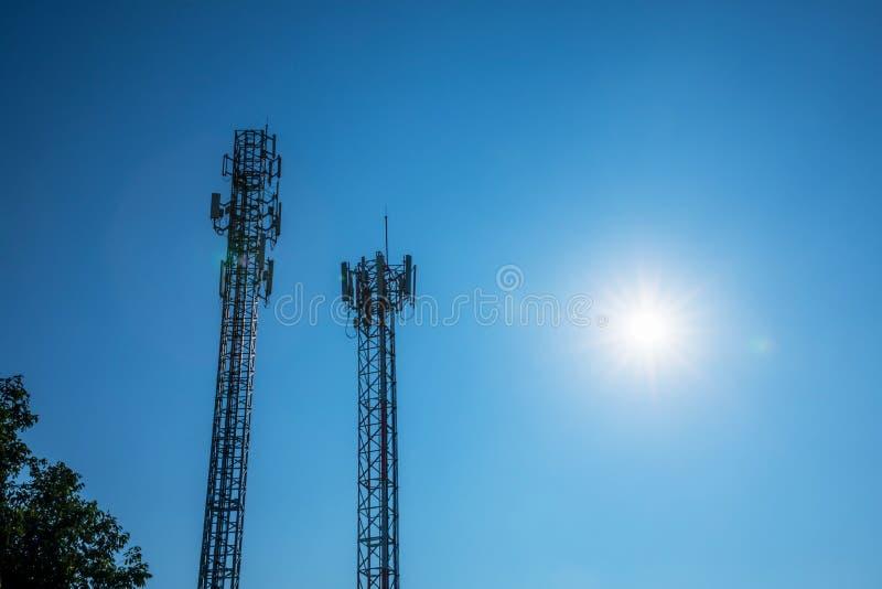 两个电信塔从日出,高塔和标志coveri的剪影美好的光传导的 免版税库存图片