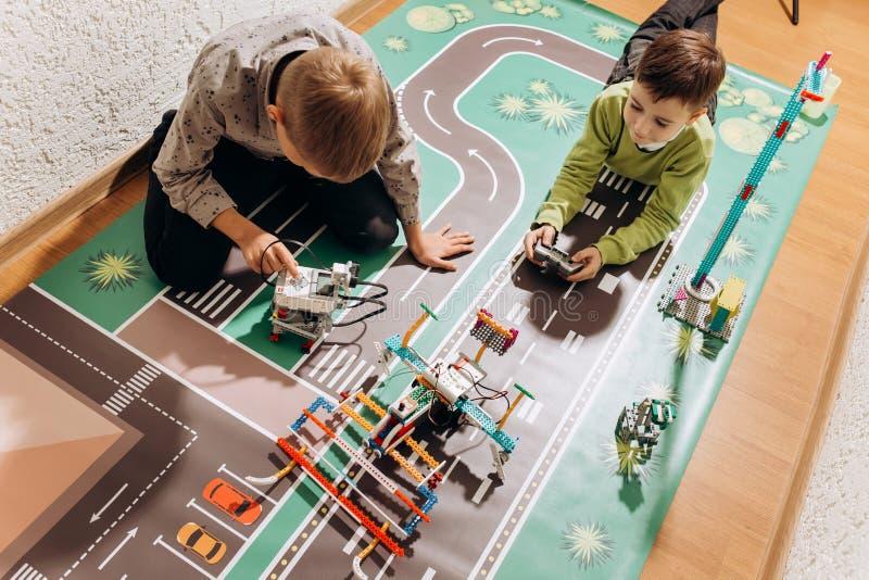 两个男孩使用与他们从在五颜六色的横幅的机器人建设者创造在地板上在的机器人 图库摄影