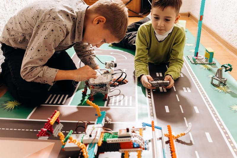 两个男孩使用与他们从在五颜六色的横幅的机器人建设者创造在地板上在的机器人 库存图片