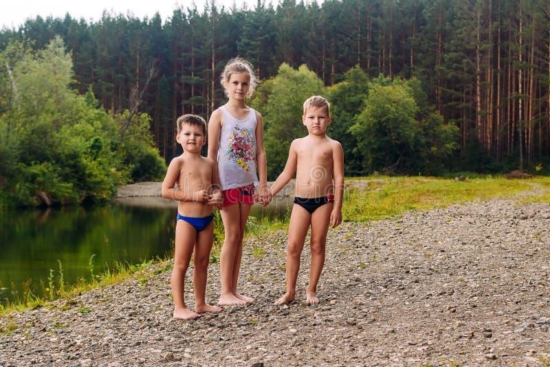 两个男孩和一个女孩河的河岸的在夏天 免版税图库摄影